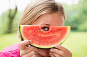 Close up portrait of girl peering through watermelon slice