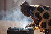 Herero woman bending over a smoking grill, Sesfontain, Namibia
