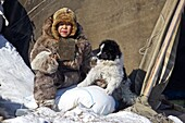 nomad child dressed in reindeer skins with a young dog, Chukotka Autonomous Okrug, Siberia, Russia