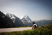 Cyclist taking a rest on a mountain pass, Eiger and Moench in the background, descent from Grosse Scheidegg to Grindelwald, Bernese Oberland, Switzerland
