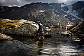 Man wading through a mountain lake, near Bremer Hütte (ca. 2413 m), rear of Gschnitz Valley, Stubai Alps, Tyrol, Austria