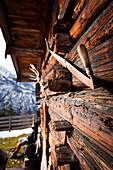 Wooden hut and hiker taking a rest, descent from Unnutz Mountain (2078 m), Rofan Mountains, Tyrol, Austria