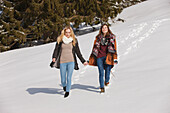 Two young women walking hand in hand in snow, Spitzingsee, Upper Bavaria, Germany