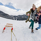 Two young women running in snow, Spitzingsee, Upper Bavaria, Germany