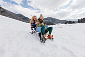 Two young women downhill sledding, Spitzingsee, Upper Bavaria, Germany