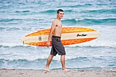 Teen surfer with his surfboard