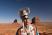 Navajo Indian dressed in a traditional costume, in background is Merrick Butte right and East Mitten Butte left, Monument Valley Navajo Tribal Park, Arizona, USA