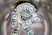 US dollars in a sink drain  Money going down the drain concept