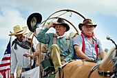American settlers in a wagon at a 4th of July parade