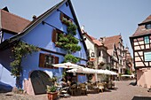 Riquewihr, Alsace, Haut-Rhin, France, Europe  A la Couronne restaurant in old building on narrow cobbled street with people dining outside in picturesque medieval town on the Alsatian wine route