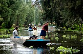 Residents ride in a boat through the water canals of Xochimilco on the south side of Mexico City. The water canals and gardens in Xochimilco was once part of the Americas breadbaskets and the agricultural hub of Tenochtitlán Aztec empire The water canals