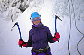 Young woman ice climbing in Pyhä, Lapland, Finland.