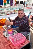 Turkish man selling fresh orange juice using a fruit squeezer at the bazaar in Belek, Turkey