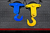 Bold colored industrial crane hooks used for lifting heavy objects against a black and white brick wall.