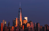 One World Trade Center commonly referred to as the Freedom Tower and other Financial District skyscrapers are bathed in golden light during the last light at sunset.