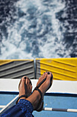 Woman's feet on the seat of a deck ferry with the waves at the background, Milos, Cyclades Islands, Greek Islands, Greece, Europe.