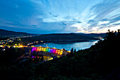 Edertalsperre dam at Lake Edersee in Kellerwald-Edersee National Park illuminated by a colorful light installation at dusk, Lake Edersee, Hesse, Germany, Europe