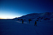 People walking through the snowy Spitzbergen in the night, Spitzbergen, Svalbard, Norway