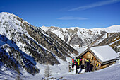 Several persons back-country skiing standing in front of alpine hut, Frauenwand, valley of Schmirn, Zillertal Alps, Tyrol, Austria