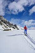Woman back-country skiing walking towards snow-covered alpine hut, Monte Faraut, Valle Varaita, Cottian Alps, Piedmont, Italy