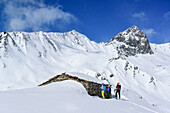 Three persons back-country skiing standing in front of alpine hut, Tete dell'Autaret and Pelvo di Ciabriera in background, Monte Faraut, Valle Varaita, Cottian Alps, Piedmont, Italy