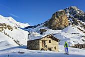 Woman back-country skiing ascending towards Monte Salza, crossing alpine hut, in the background Rocca Senghi, Monte Salza, Valle Varaita, Cottian Alps, Piedmont, Italy