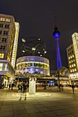 World clock at Alexanderplatz and view towards Alex at night, Berlin, Germany