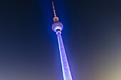 Colourfully illuminated TV tower Alex at night, Berlin Alexanderplatz, Berlin, Germany