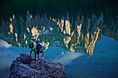 two mountain bikers at lake Karersee with reflection of Latemar, Trentino Italy