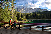 two mountain bikers on an observation platform at lake Karersee, Latemar massif in the background, Trentino, Italy