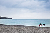 A family on the pebble beach of Birdlings Flat at Banks Peninsula, Christchurch, South Island, New Zealand
