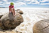 A girl sitting on a Moreaki Boulder with the rising tide, Moeraki Boulders, South Island, New Zealand
