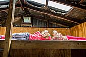 Zwei Mädchen auf dem Bett einer Hütte, Tramping Fjordland, Lake Manapouri, Südinsel, Neuseeland