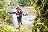 A girl traversing a rope bridge, a walk wire at Lake Manapouri, Fjordland, South Island, New Zealand