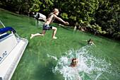 Zwei Mädchen springen ins Wasser, Motorboot in der Bucht Falls Creek. Abel Tasman Nationalpark, Südinsel, Neuseeland