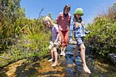 Zwei Mädchen und eine Frau waten barfuss in einem Bach, Abel Tasman Nationalpark, Südinsel, Neuseeland