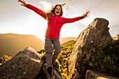 Ein Mädchen springt von einem Felsen, Castle Rocks, bei der Castle Rock Hut, Abel Tasman Nationalpark, Südinsel, Neuseeland