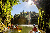 Two girls and a woman on a canoe trip on the Whanganui River, North Island, New Zealand