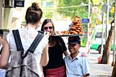 Tourists and Vietnamese man carrying food on his head, Saigon, Ho Chi Minh-City, Vietnam, Asia