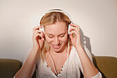 Junge Frau sitzt auf dem Sofa und hört Musik
