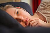Junge Frau entspannt sich auf dem Sofa, Nachdenklich