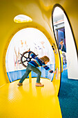 Young boy playing at submarine playground, Cuxhaven, North Sea, Lower Saxony, Germany