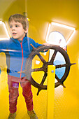 Young boy playing in a submarine at the playground, Cuxhaven, North Sea, Lower Saxony, Germany