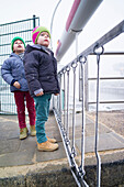 Boys looking over a level-crossing, Cuxhaven, North Sea, Lower Saxony, Germany