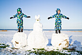 Boys playing on a huge snowball, Cuxhaven, North Sea, Lower Saxony, Germany