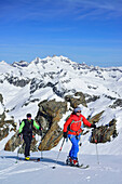 Two persons back-country skiing ascending towards Dreiherrnspitze, Gabler and Reichenspitze in background, Dreiherrnspitze, valley of Ahrntal, Hohe Tauern range, South Tyrol, Italy