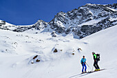 Two persons back-country skiing standing at glacier of Dreiherrnspitze, Dreiherrnspitze, valley of Ahrntal, Hohe Tauern range, South Tyrol, Italy