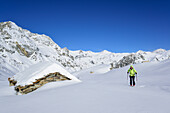 Woman back-country skiing passing snow covered alpine hut with Monte Gabel in background, Rocca La Marchisa, Valle Varaita, Cottian Alps, Piedmont, Italy