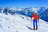 Woman back-country skiing ascending towards Halslspitze, view to Zillertal Alps with Rosswandspitze, Grosser Loeffler and Grosser Moerchner, Halslspitze, Tux Alps, Tyrol, Austria