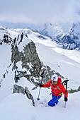 Woman back-country skiing ascending on ridge towards Grundschartner, Grundschartner, Zillergrund, Zillertal Alps, Tyrol, Austria
